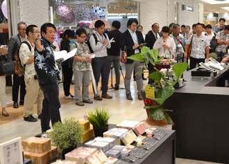 すでに商品が並べられた那覇オーパの店内で報道陣を案内する比嘉館長(手前左)=那覇市泉崎