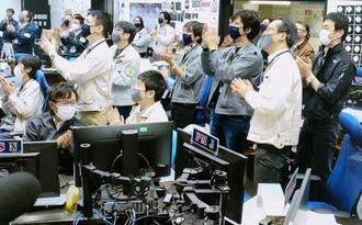 大気圏突入したカプセルが出す追跡用電波の受信を確認し、管制室で喜ぶJAXA関係者の映像=6日午前2時30分、相模原市