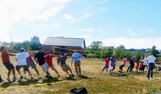 男女に分かれて綱引きを楽しむピクニックの参加者たち=米ニュージャージー州
