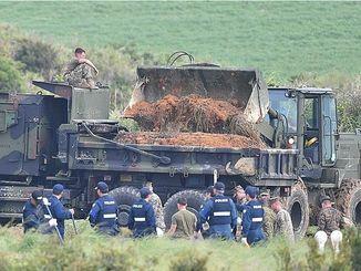 重機で土壌を掘り返し、トラックに運び込む米軍関係者=20日午後5時、東村高江