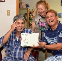 又吉直樹さんサイン入りの「火花」を手に芥川賞受賞を喜ぶ(左から)父己敏さん、伯母初美さん、叔父洋一さん=16日、名護市汀間