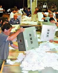 一斉に投票箱を開け、開票作業をする名護市の職員=9日午後9時すぎ、名護市民会館