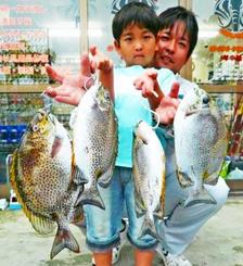 西崎海岸で41センチ、1.44キロのカーエーを釣った大屋義樹さん(奥)と琉來さん=9日
