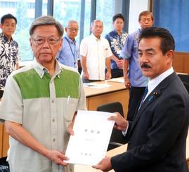 佐藤外務副大臣に日米地位協定の見直し要請書を渡す翁長知事(左)=12日、外務省