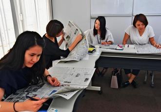 紙面を見ながら気になる記事を探す受講者ら=7日、那覇市の電通沖縄