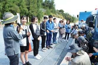 新基地建設に抗議して座り込む市民を激励する韓国の市民団体「平和の風」の沖縄訪問団(左側)=20日、名護市辺野古・キャンプシュワブゲート前