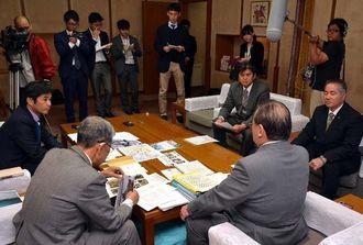 提出した資料を安慶田光男副知事(手前右)に説明する名護市議会の議員ら=5日、県庁