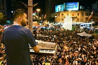 反政府デモを音楽で盛り上げる男性=16日、レバノン北部トリポリ(共同)