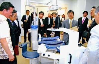 新たに設けられた手術室を見学する関係者=13日午後、南風原町新川・県口腔保健医療センター