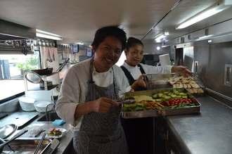レストランバスの1階で食事を準備する比嘉康洋シェフ(左)