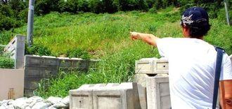 太陽光パネルの設置予定地とされる場所を指さす元従業員の男性=8月21日、沖縄本島中部