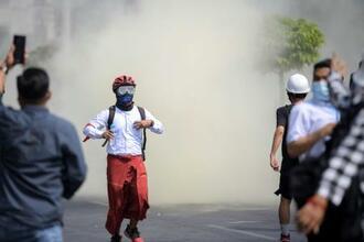 27日、ミャンマー・ヤンゴンで、催涙ガスから逃げるデモ参加者(ロイター=共同)