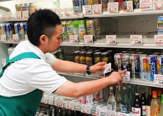 閉店後に商品の値札を貼り替える店員=31日午後10時30分ごろ、那覇市・天久りうぼう