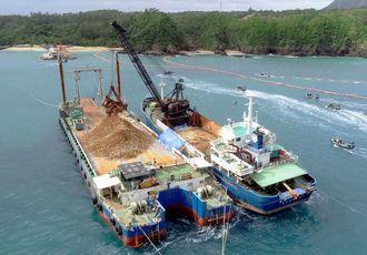 運搬船(右)から台船へ土砂を移し替える作業が進められた。左奥は「K9」護岸=12日午前11時分、名護市辺野古(小型無人機で撮影)