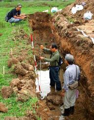 重機で掘削して表れた地層を調べる研究者ら=2013年11月、石垣市伊原間(安藤雅孝客員教授提供)