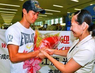 出迎えた関係者から花束を受け取る江藤光喜(左)=那覇空港