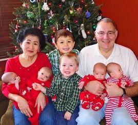 昨年10月に生まれた4つ子の孫を抱く里子さん(後列左)とカールさん(同右)夫妻と長女クリスさんの子供たち