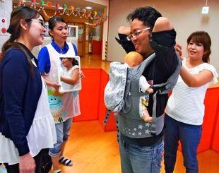 又吉笑子さん(右)の指導で、抱っこひもの装着に挑戦する新里大樹さん(同2人目)。手前左は妻の鮎美さん=8月25日、宜野湾市・HAPPYひろば