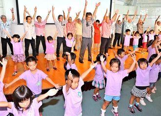 しまくとぅばに合わせてラジオ体操をする高良倉吉副知事らと大山幼稚園の子どもたち=9月18日午後、宜野湾市・沖縄コンベンションセンター