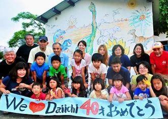 共同制作した恐竜の壁画前で、記念撮影におさまる友寄第一団地自治会の住民たち=11日、八重瀬町友寄