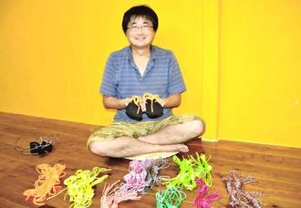 ゴム製のソールにひもを通した「ワラーチ」作り体験をPRする坪谷昌二さん=19日、市大川のユーグレナモール