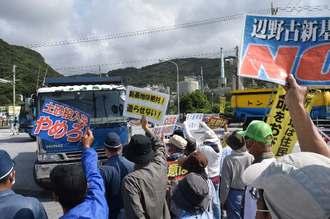 土砂を搬入するダンプカーに抗議する市民ら=15日午前9時半ごろ、名護市安和の琉球セメントの桟橋入り口
