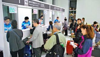 出国手続きの案内を受けるニュージーランドチャーターのツアー客=19日、那覇空港国際線ターミナルビル