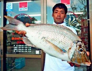 安謝の海岸で61センチ、2.82キロのタマンを釣った比嘉一歩さん=23日