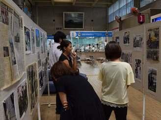 米軍ヘリ墜落事故当時の写真や資料などに見入る人たち=宜野湾市役所