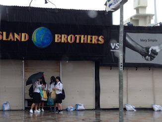 早々と店じまいした店舗の軒下で雨宿りする学生ら=4日午後3時すぎ、那覇市の国際通り