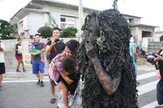 パーントゥに泥を塗られ、カメラを向ける観光客ら=3日、宮古島市平良島尻