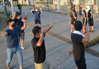 綱引きの前に歌を歌い輪になって踊る住民ら