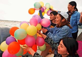 対話の象徴として持参したカラフルな風船を船上からたなびかせる若者たち=14日、名護市辺野古・米軍キャンプ・シュワブ沖