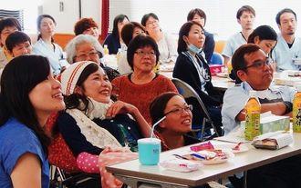 幼少期からの写真やビデオレターに笑顔を見せる當間光江さん(左から2人目)。弟の清次さん(前列右)ら親族や友人、病院スタッフも一緒に楽しんだ=4月29日、糸満市・南部病院