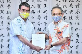 河野太郎沖縄担当相(左)に要望書を手渡す玉城デニー知事=19日午後、県庁