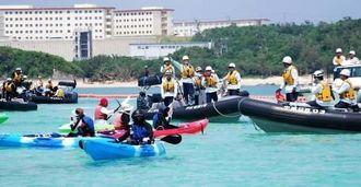 オレンジ色のフロートの前に並び、カヌー隊(手前)を排除する海上保安庁の黒色のゴムボート=13日午後1時10分ごろ、名護市辺野古沖