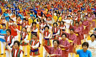 沖縄民踊フェスティバルで普及曲に合わせて一斉に踊る出演者=25日、沖縄市体育館(下地広也撮影)