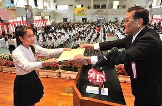 喜びの面持ちで卒業証書を受け取る卒業生(左)=23日、豊見城市高安・とよみ小学校