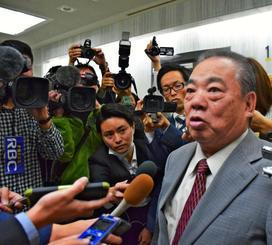 記者団の取材に答える安慶田光男副知事=18日午前11時半ごろ、沖縄県庁