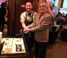 4周年を祝いケーキカットする上地店長(左)と県人会の神山吉洋会長=カナダ・トロント市内