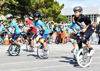 ゴールを目指して懸命に一輪車をこぐ児童=9日、名護市民会館駐車場