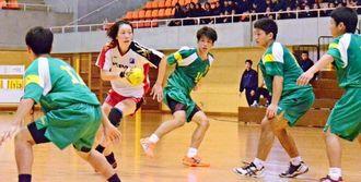 コザ高男子の陣営に攻め込む女子日本代表の東濱裕子(左から2人目)=沖縄市体育館