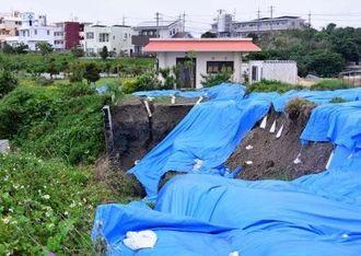 避難勧告が出されたレストラン(中央)と崖崩れの現場=13日、中城村奥間