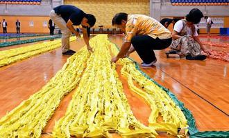 折り鶴ロープを計測し、ギネス認定となった=7日午後、沖縄市体育館(喜屋武綾菜撮影)