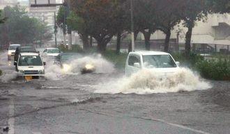 道路が冠水し、水しぶきを上げながら通行する車両=午後3時20分ごろ、那覇市上間