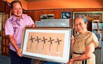 生まれ育った大宜味村に手織りの芭蕉布を寄贈した平良敏子さん(右)。受け取る宮城功光村長=7日、大宜味村役場
