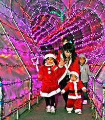 サンタの衣装でイルミネーションのアーチを歩く家族連れ=23日午後、沖縄市胡屋・沖縄こどもの国(山城知佳子撮影)