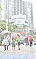 雨の中、傘をさして歩く人たち=3日午後1時すぎ、那覇市久茂地