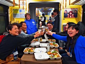 比嘉酒造の創立70周年イベント「ZANPA TRAIN」で泡盛を楽しむ参加者ら=10日、ゆいレール車内