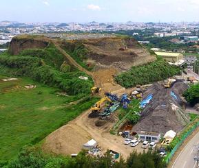 倉敷環境が積み上げたごみ山。左側の緑地も以前はごみ山だった=8月31日、沖縄市池原(小型無人機から)
